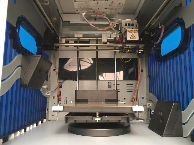 L'intérieur de la Da Vinci 1.0 Ai0. Les deux blocs noirs (en bas à droite et au milieu à gauche) permettent de scanner les objets placés sur le plateau rotatif (visible en bas de la photo).