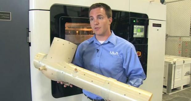 Kyle Whitlow, ingénieur chez ULA tient le système de conditionnement imprimé en 3D à l'aide de la Fortus 900mc (en arrière plan).
