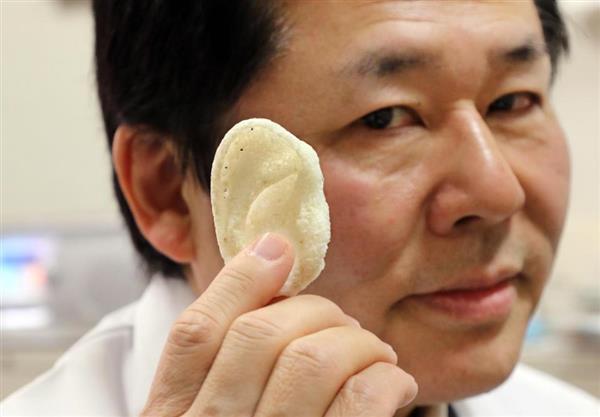 Le Pr. Tsuyoshi Takato de l'université de Tokyo tient une oreille imprimée en 3D